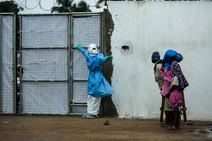 A family waits at the entrance to Island Clinic in Monrovia, Liberia, which was opened by the World Health Organization and the Liberian Ministry of Health in response to the surge of patients needing an Ebola Treatment Unit. Here, a health worker in protective gear tells the family to wait on the side as they open the doors for an ambulance to exit the facility. Before the facility opened on September 21, ambulances and patients arrived at the gates waiting to be admitted. Just a day after opening, the clinic is already at capacity. USAID has provided two generators and other supplies to equip the facility with life-saving care.