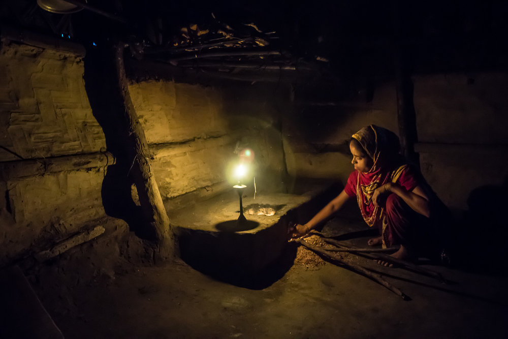 COX'S BAZAR, BANGLADESH: October 25, 2016 - Joynur's mother, Shahena Akter, 24, lights the fire in the morning to make breakfast and tea for the family. Photo by Morgana Wingard