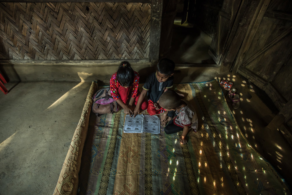 COX'S BAZAR, BANGLADESH: October 25, 2016 - When Joynur's mother is busy with cooking, Joynur helps her younger brother and sister with their studies. Photo by Morgana Wingard