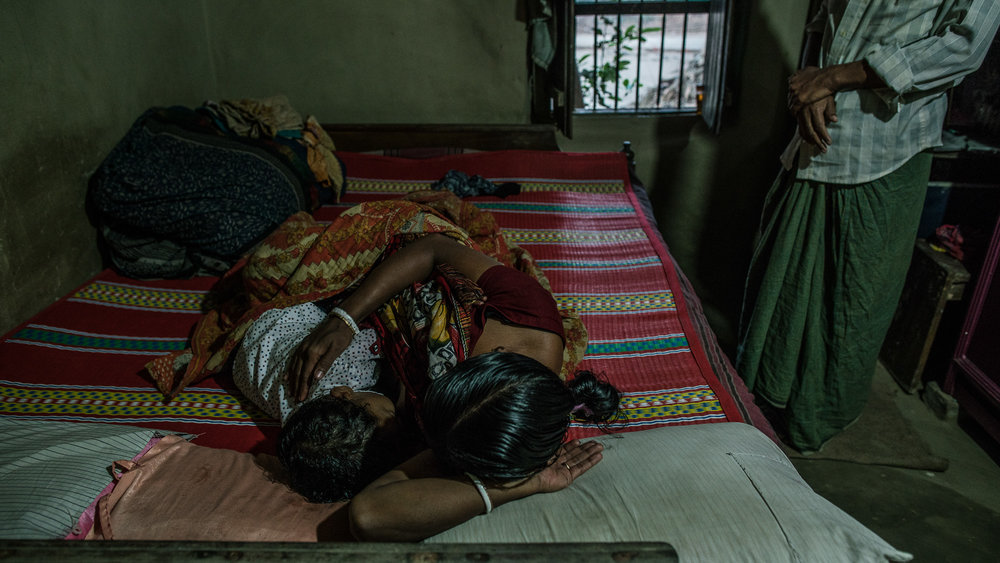 Supriya Dae (mother) and her husband, Rotonu Dey, wake up their son, Ornoy Dey in the morning.