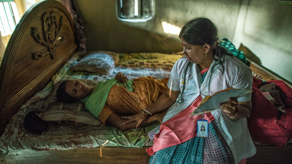 Shanta Das, a paramedic at Smiling Sun Clinic, consults a pregnant mother at her home.