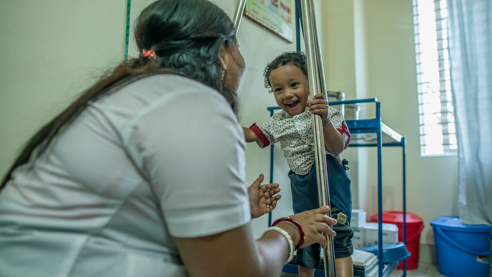 Supriya Dae and her son visit paramedic, Shanta Das, for a checkup on his growth.