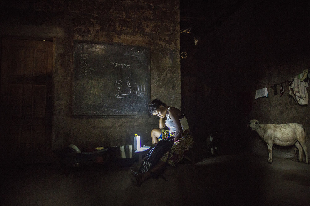 Mariatu Bangura, 18, of Rokupr, studies at her home in the evening.