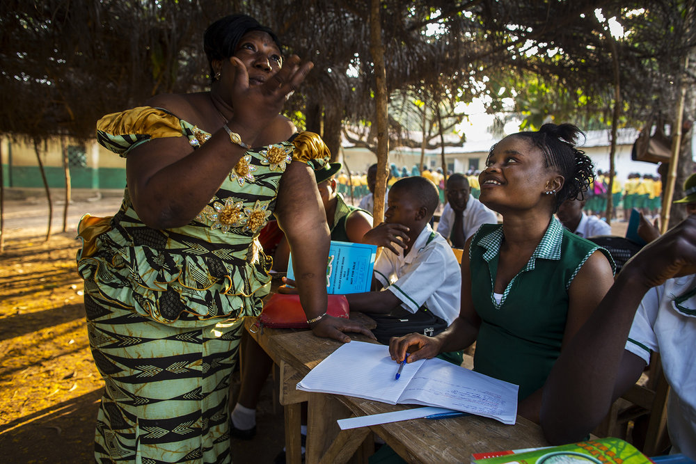 Mabinty Kubra Turay, left, Manager of Kubra Agricultural Secondary School, talks with Mariatu Bangura, 18, of Rokupr, before class begins. Mabinty helped Mariatu return to regular school after she attended the remedial school following the birth of her son.