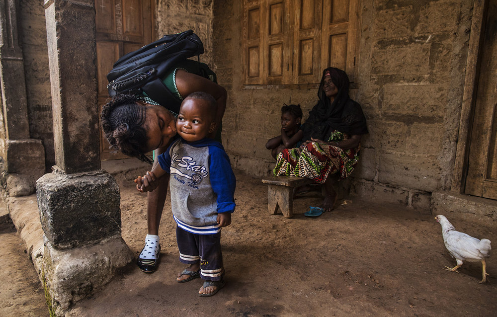 Mariatu Bangura, 18, of Rokupr, left, kisses her son, Abduli, before going to school. Abduli stays with Mariatu's grandmother, Yamaya Kamara, back right, while she attends school. Also pictured on back left is Mariatu's cousin, Ya Alimamy Kamara.