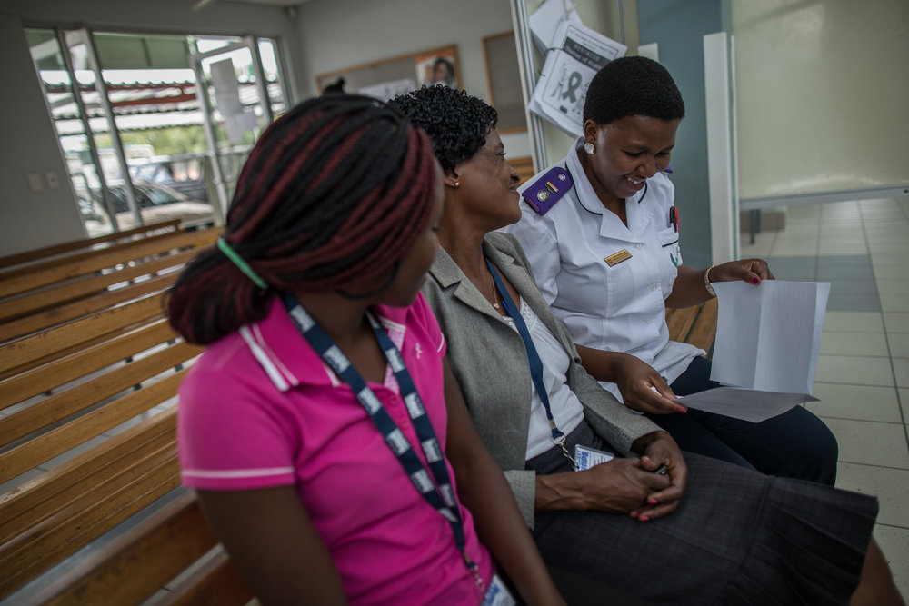 Loide Likuyu (center) talks with health workers at Shanamutango HIV clinic at Onandjokwe Hospital, Namibia.