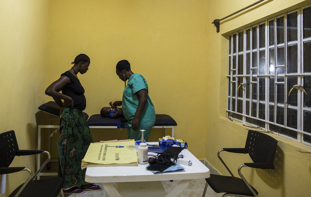 Zainab Tity Sawaneh, Maternal and Child Health Aide, right, examines a patient during the evening. Konsho CHP is now equipped with solar power.