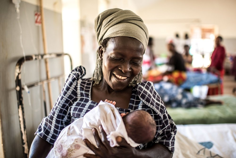 Dioweri Kalikumadi smiles as she holds her one-day old granddaughter in the maternity ward of the Jinja Regional Referral Hospital.