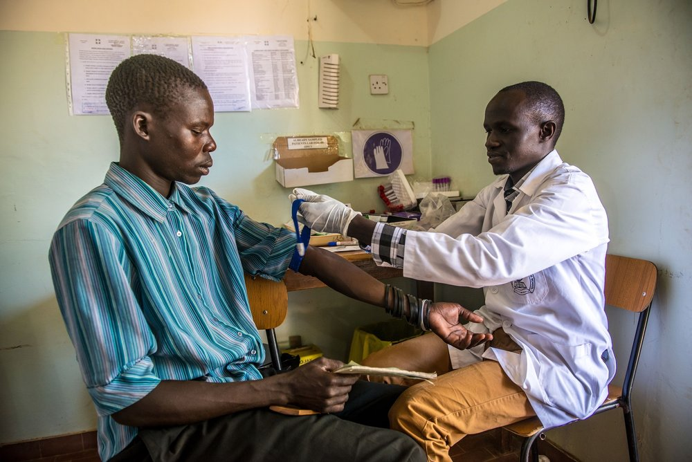 Lab Assistant David Modo takes a blood sample from a patient at the Matany hospital in Karamoja, Uganda.