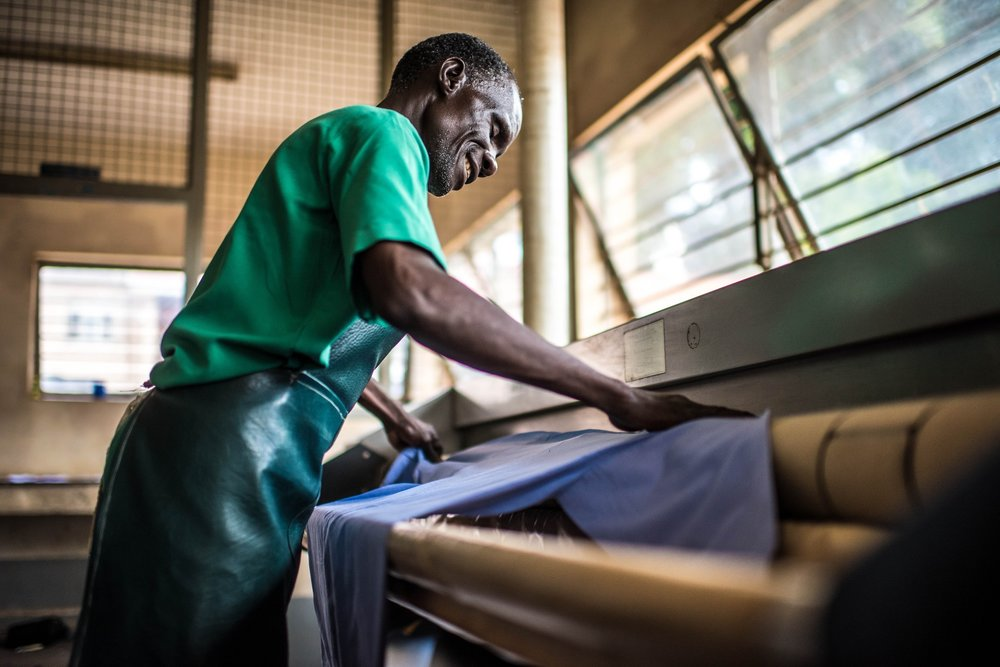 Omiat Mackay, a staff member of the Soroti Regional Referral Hospital, processes the laundry.