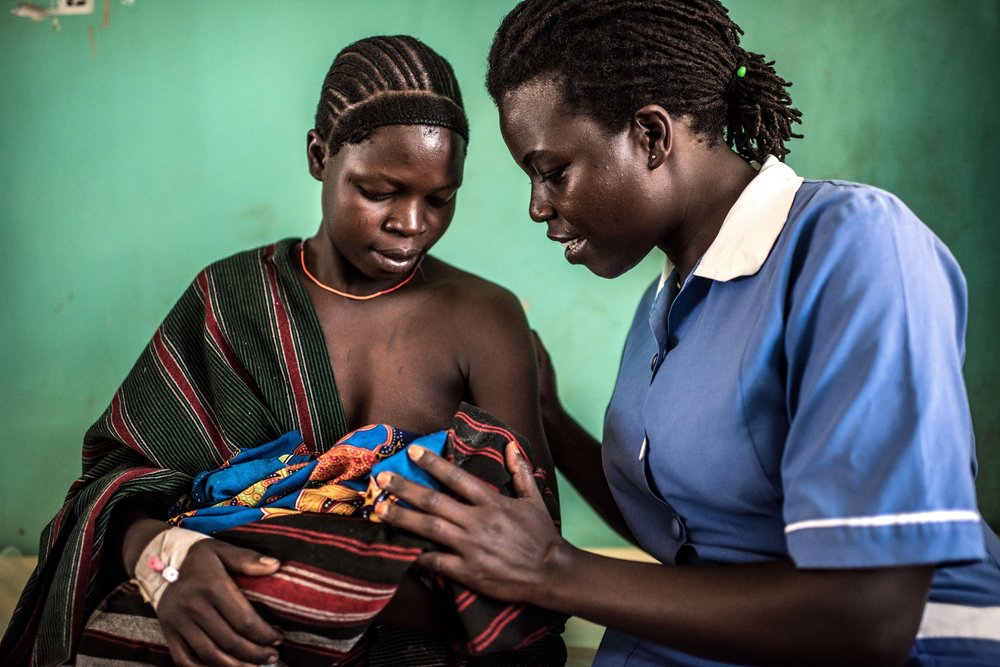 Munges Veronica, 24, holds her newborn baby, Teko, with Atim Jane, a 38 year old nursing officer at the Nadunget Health Center 3 in Karamoja, Uganda.