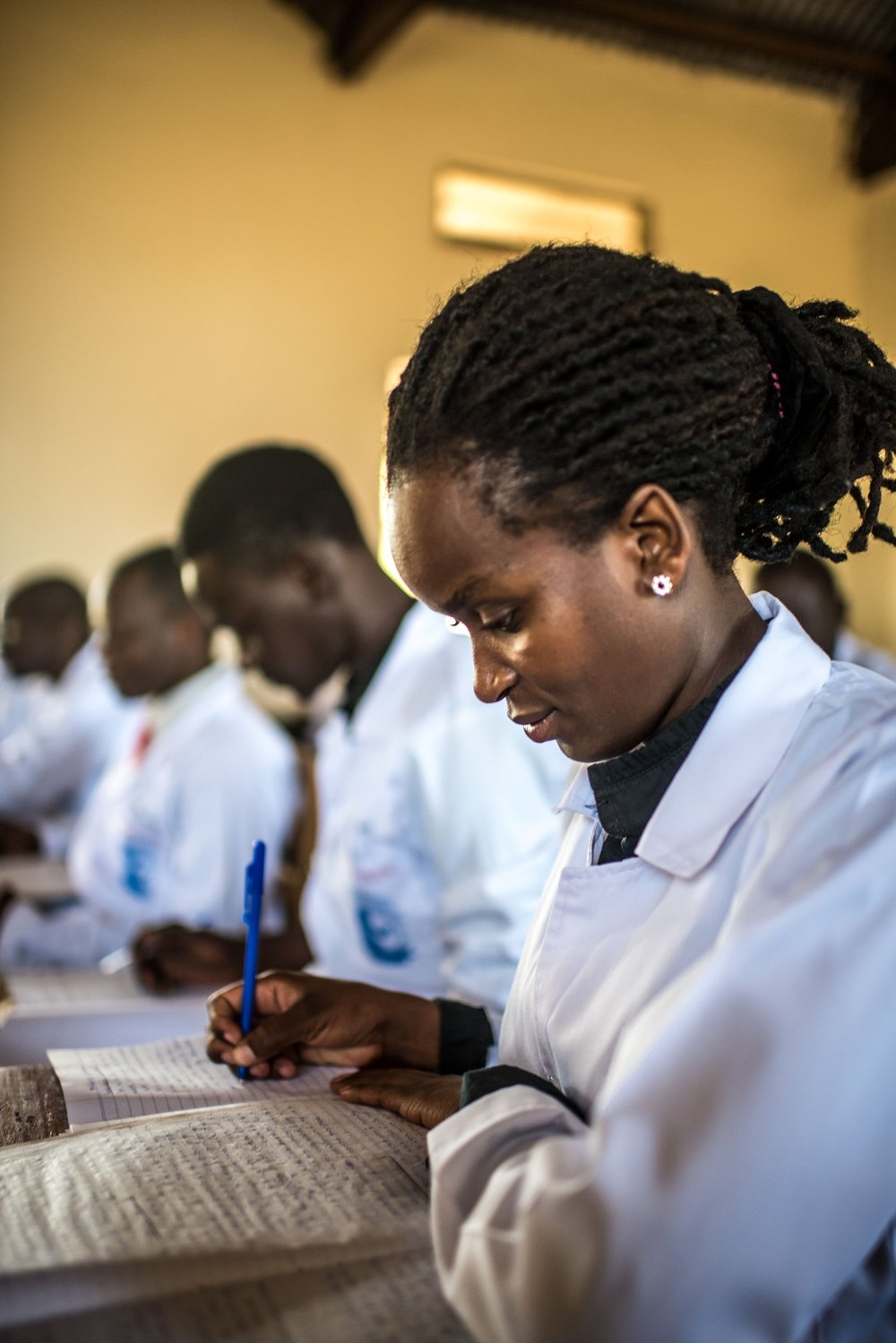 Nikiria Caoline, 21, a student of the Soroti Pharmacy School, takes notes during a class.