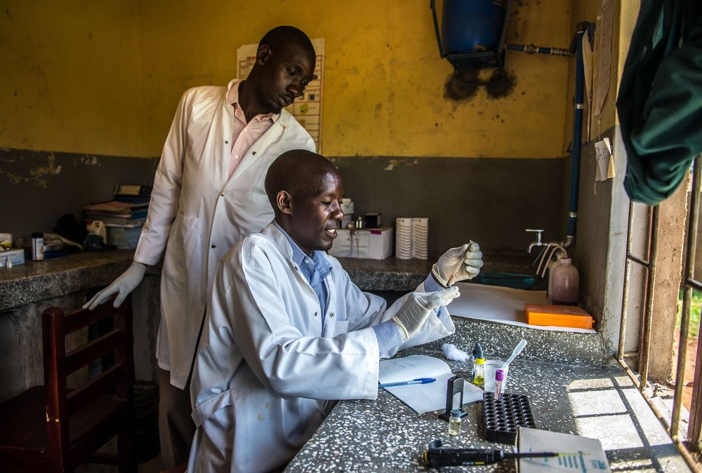 Mwiru Ali, a lab assistant, inspects a blood sample at the Busowobi health center in Iganga District, Uganda.