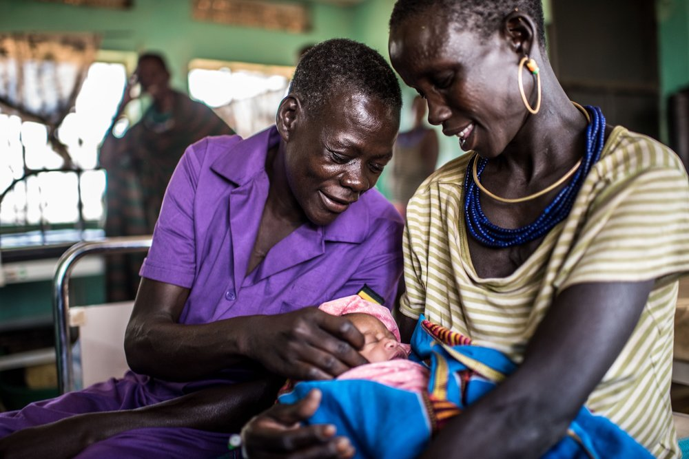 Najore Ruth, 45, a nursing assistant, sits with Angolere Lucy, who had her fifth baby overnight in the maternity ward of the Nadunget Health Center 3 in Karamoja, Uganda.