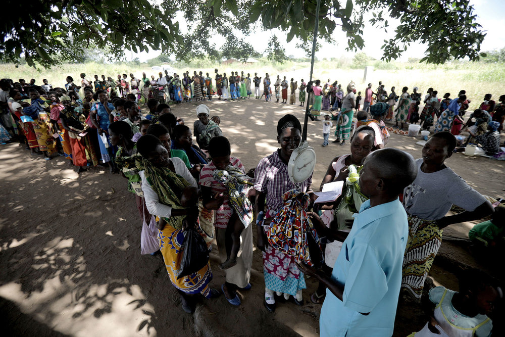 "Women began to gather under the shade of a large tree in TA Nsamala, with baby's on their backs. The program implemented by the government and supported by UNICEF is part of the ""improvement of nutritional and health situation for children under 5, women, internally displaced persons and refugees."" Photo by Josh Estey."
