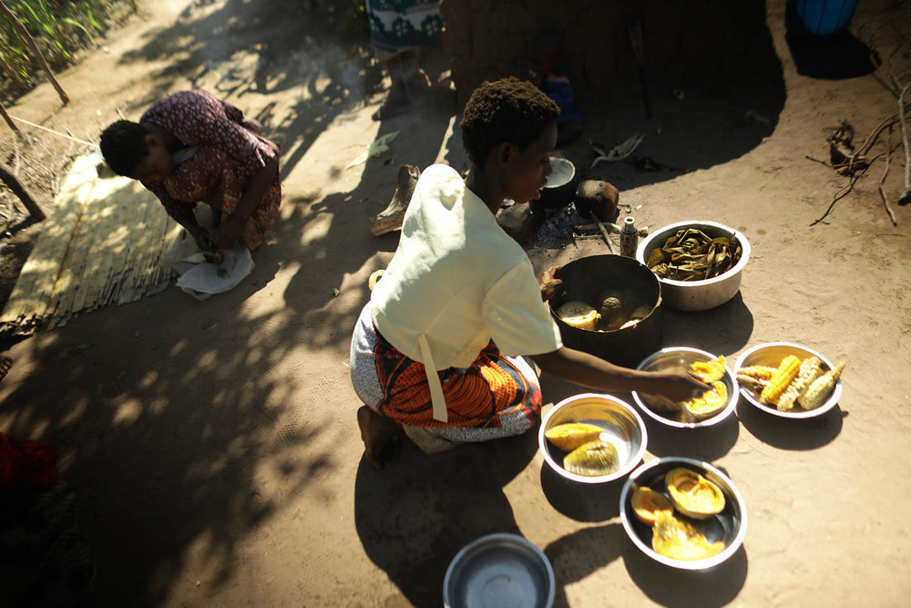 A woman prepares food near Mariam Chinguwo's house. Photo by Josh Estey