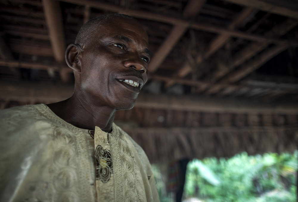 Garmondah Banwon, an elder in the Jogbahn Clan, stands in his kitchen in Blayah Town. The Jogbahn Clan fought against the British-owned company Equatorial Palm Oil (EPO) when they tried to take over their land in 2013. The people in the community depend on the land for their livelihoods. The Sustainable Development Institute (SDI) started to help the community by submitting a formal complaint to the to the Roundtable on Sustainable Palm Oil (RSPO). SDI taught the clan about land rights and resisting with non-violence. THE RSPO determined that the land EPO was using belonged to the clan. SGI trained the community how to map their land and boundaries were created that EPO accepted not to cross. Photo by Sarah Grile.
