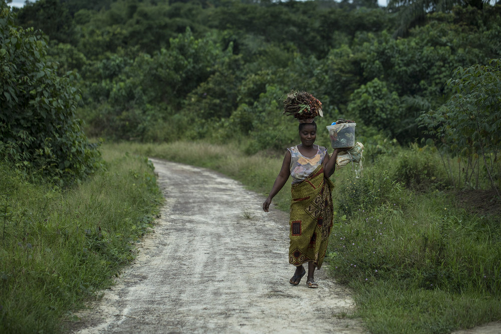 A woman walks down a road in Blayah Town, where the Jogbahn Clan reside. The Jogbahn Clan fought against the British-owned company Equatorial Palm Oil (EPO) when they tried to take over their land in 2013. The people in the community depend on the land for their livelihoods. The Sustainable Development Institute (SDI) started to help the community by submitting a formal complaint to the to the Roundtable on Sustainable Palm Oil (RSPO). SDI taught the clan about land rights and resisting with non-violence. THE RSPO determined that the land EPO was using belonged to the clan. SGI trained the community how to map their land and boundaries were created that EPO accepted not to cross.