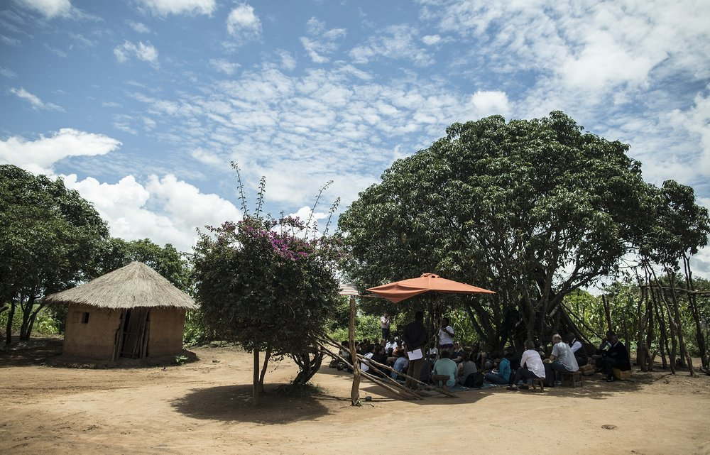 CHONGWE, ZAMBIA: Feb. 19, 2018 - Members of the CARE Learning Tour to Zambia delegation sit near the home of Memory Hachitamba while watching her participate in a SMAG home visit simulation about birth planning near the Kotaba Health Facility in Chongwe. Photo by Sarah Grile.