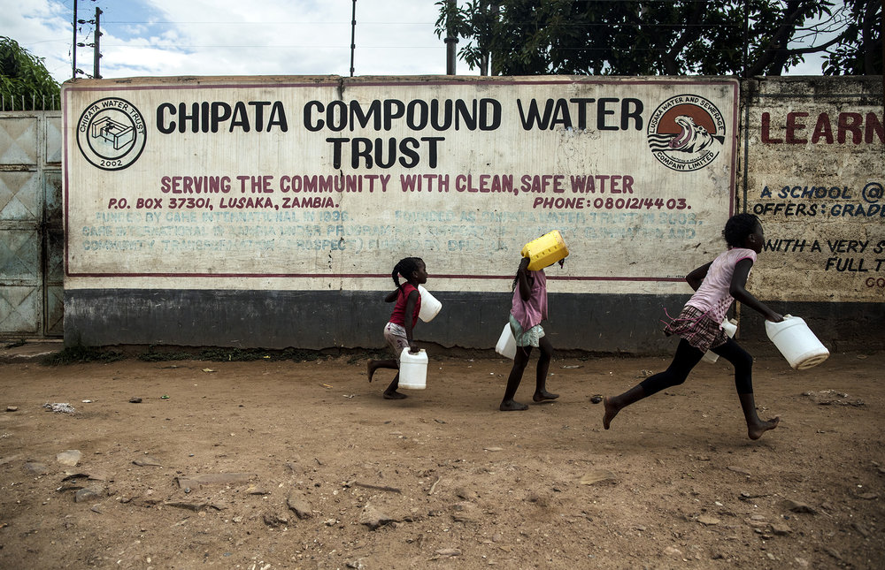 CHIPATA, ZAMBIA: Feb. 22, 2018 - CARE International Zambia and Chipata Water Trust signed a partnership agreement in 2016 to pilot the water-waste tariff bundling revenue method in the Chipata settlement of Lusaka District. CARE will provide $42,000 to the water trust over a 2 year period to support activities for facilitating the tariff bundling revenue collection method. Here, children run to collect water in front of a Chipata Water Trust sign that lists CARE as a financial supporter since 1996. Photo by Sarah Grile.