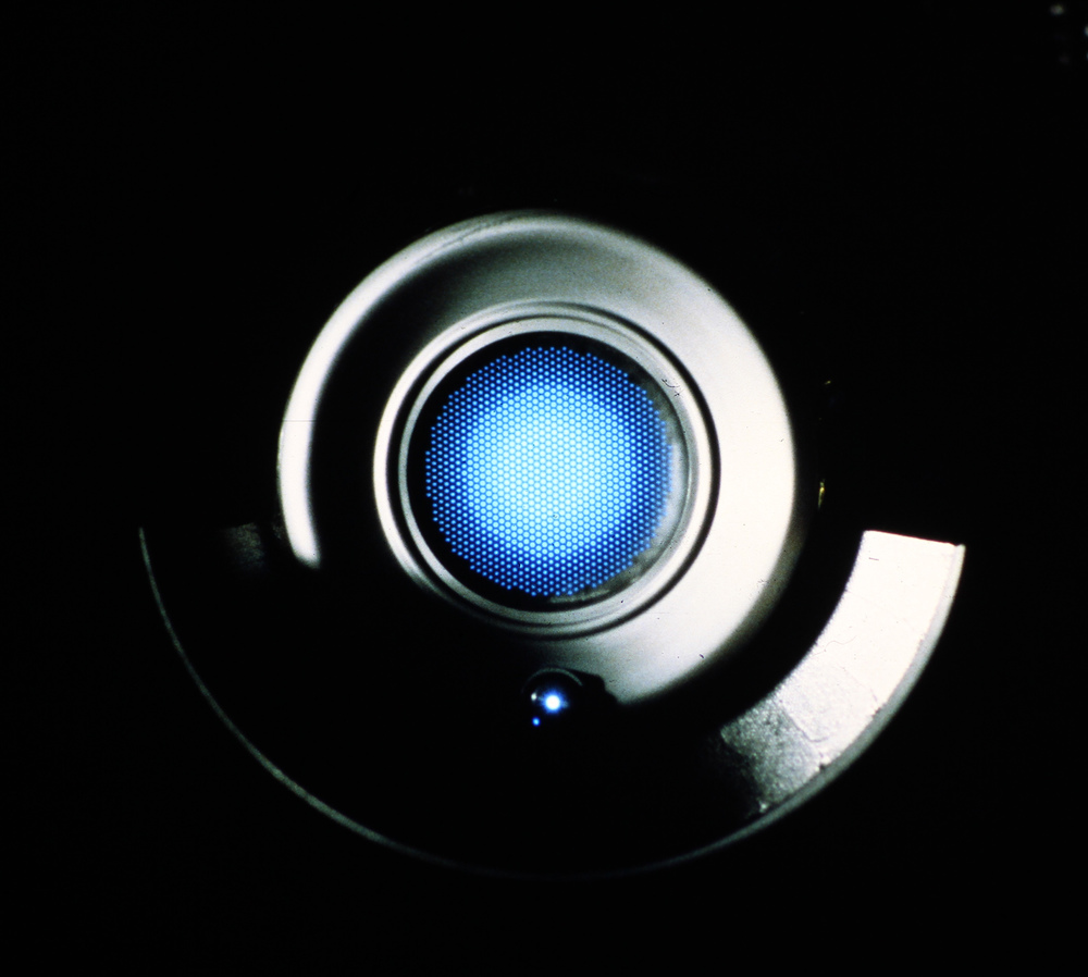 Staring into the glowing blue exhaust of a mercury-ion thruster, February 1980 James L. Long and Associates (photo)