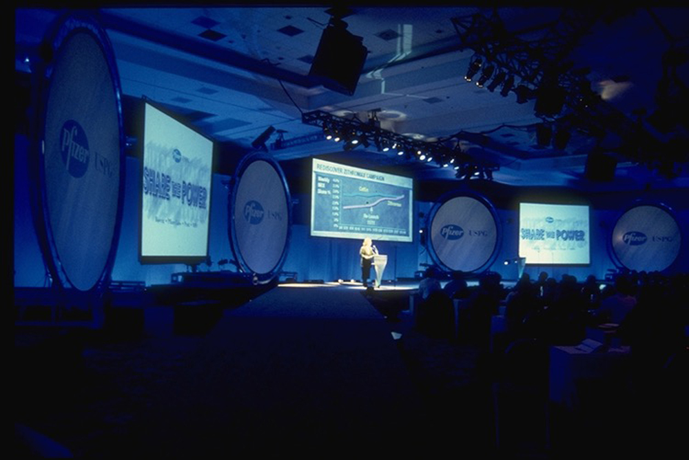 Pfizer Dealer Meeting - Rectangular & circular RP screens arrayed across a room-width stage.