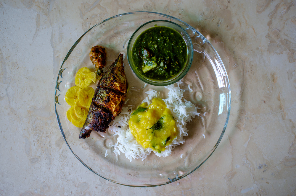 Clockwise from left: Pan-friend mackerel,  saag paneer , rice and  daal,  plantain chips
