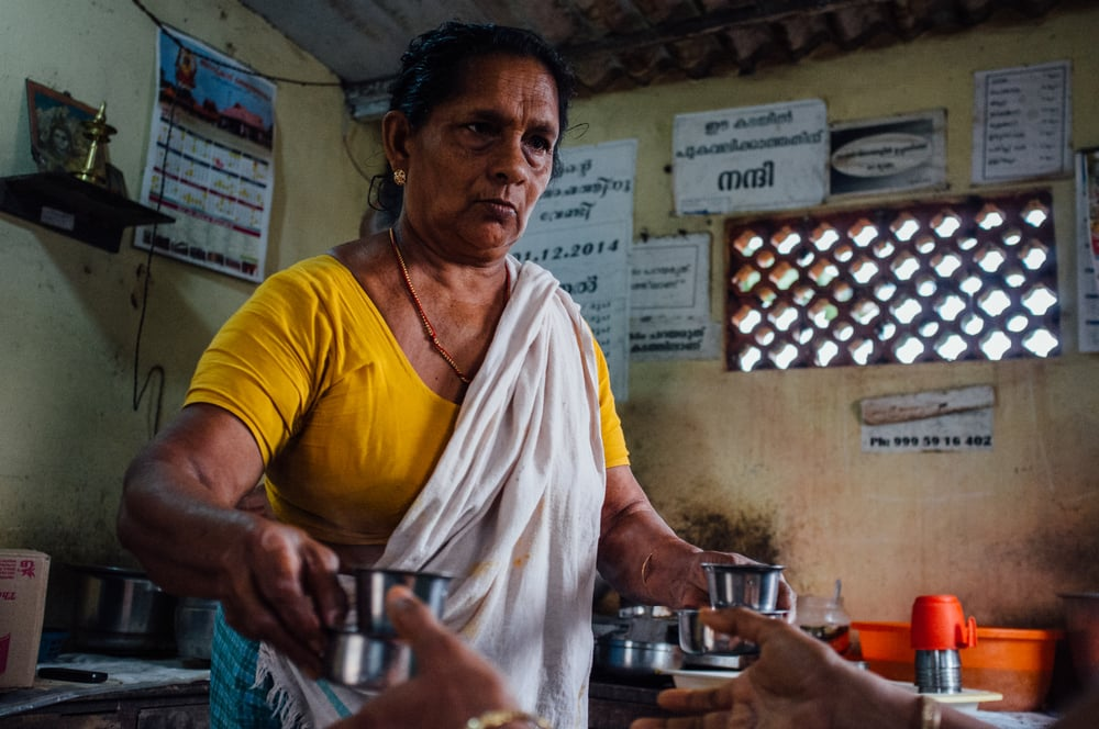 Woman serving tea at a thattukada (typically, a roadside eatery) in Pallathuruthy, Kuttanad, Kerala