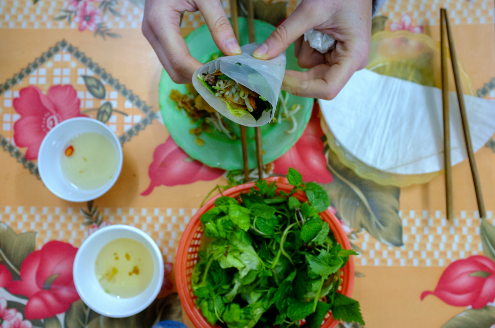 In Hanoi, bánh xèo is eaten wrapped with herbs in bánh tráng (rice paper)