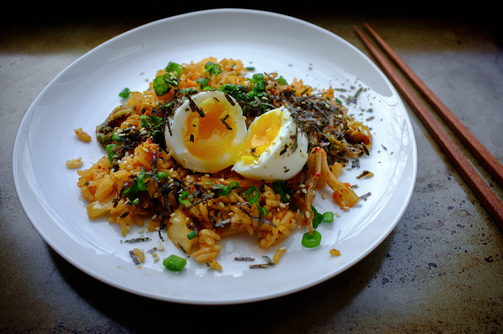 Kimchi fried rice with a soft boiled egg, garnished with shredded seaweed, sesame seeds and scallion greens