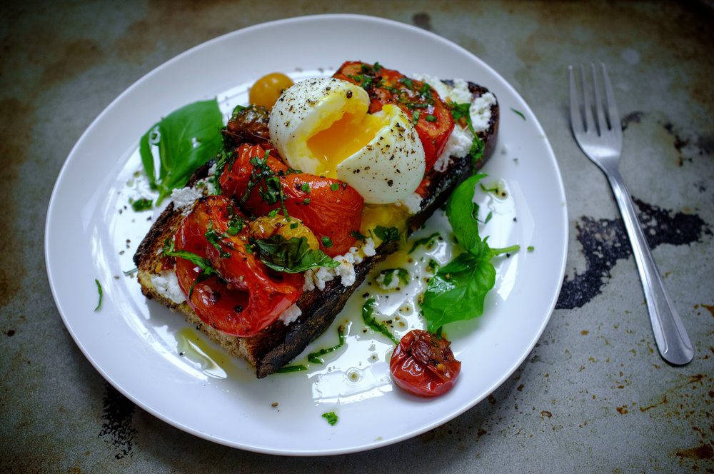 Roasted tomato tartine topped with a soft boiled egg and basil