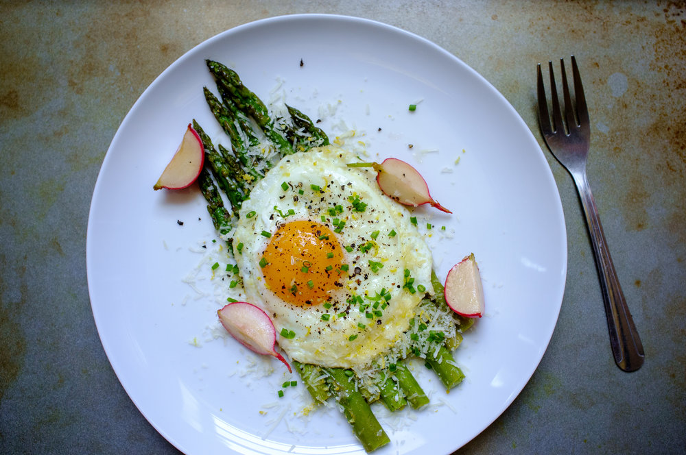 Asparagus, radishes and a fried egg, topped with parmesan cheese and lemon zest
