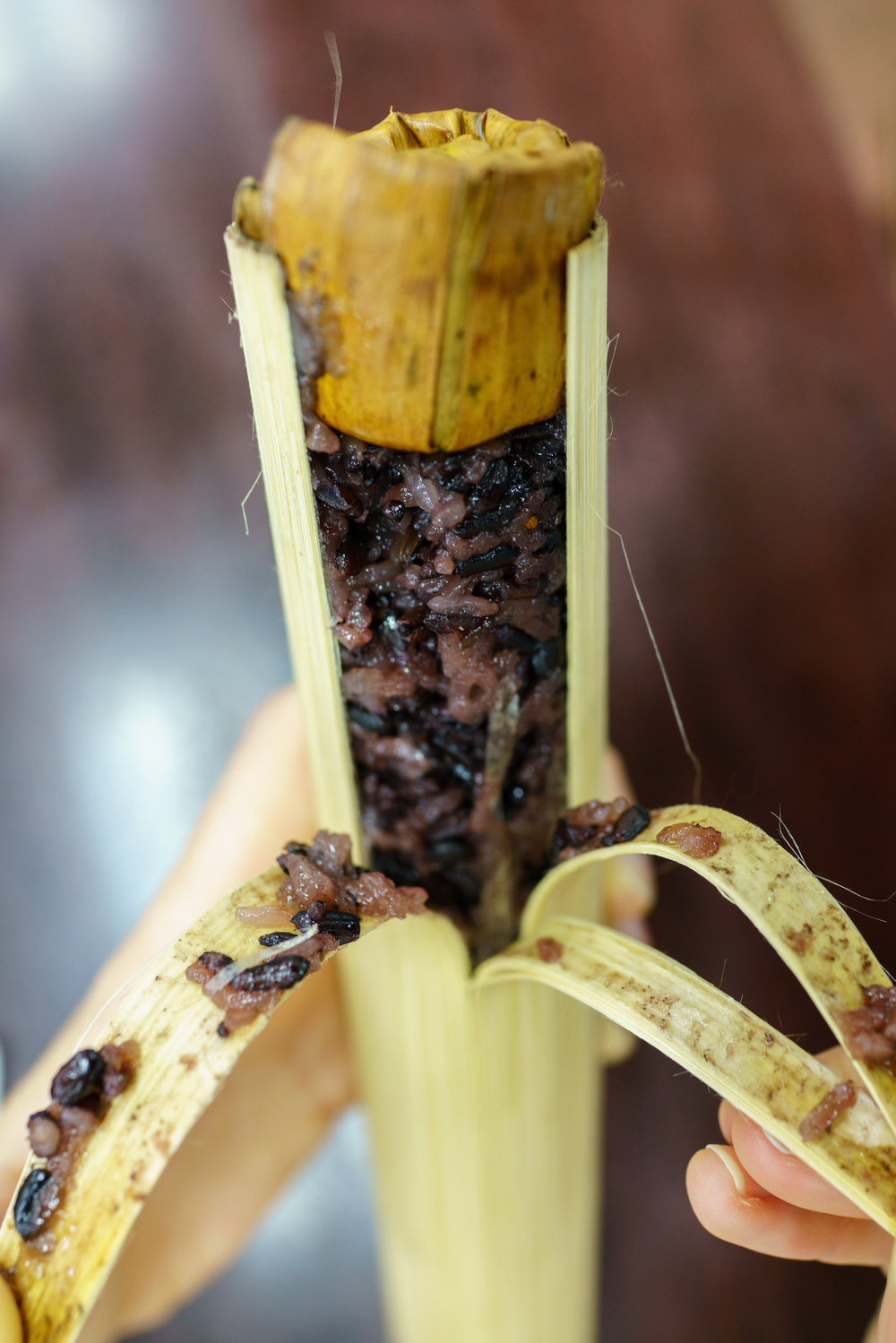 The bamboo is pulled back to reveal sweet black sticky rice