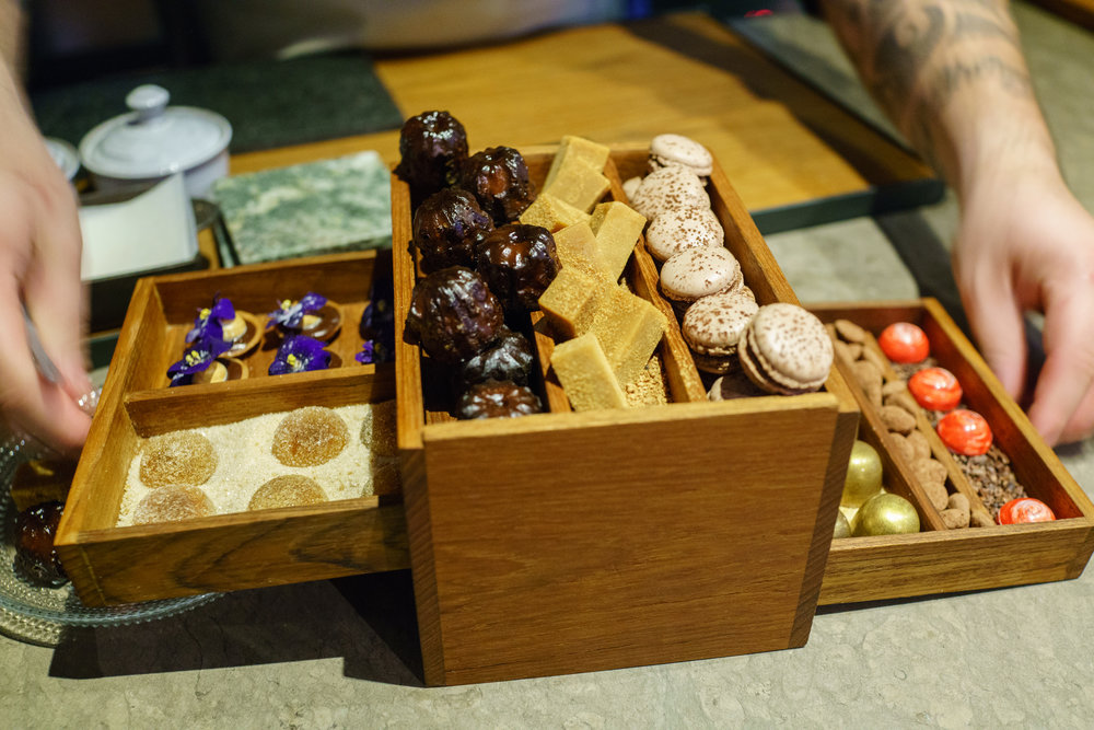 Chestnut honey canelé peeking out of the fika box at Frantzén in Stockholm