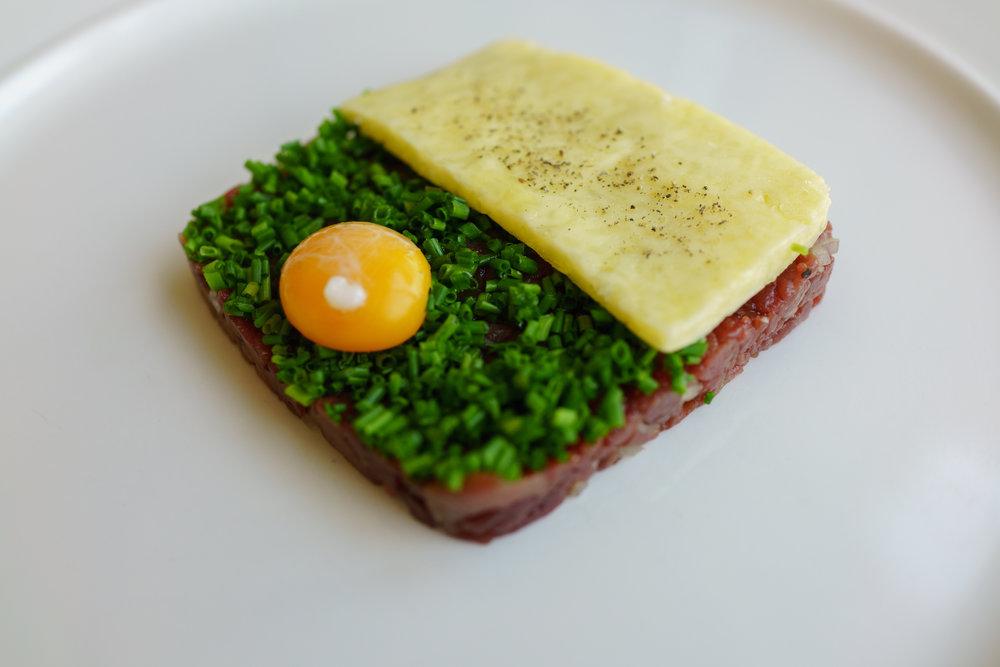 Venison tartare, fleur de sel butter, poached quail egg yolk, chives at Bistro Apetit