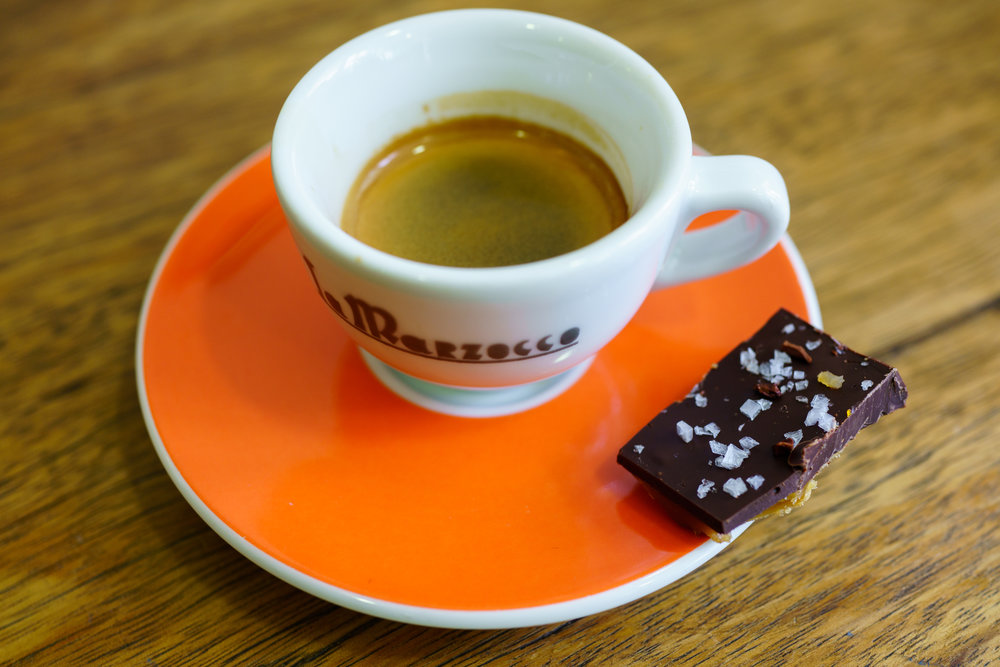 An espresso, served with a piece of chocolate bark at Bettina & Niccolò Corallo