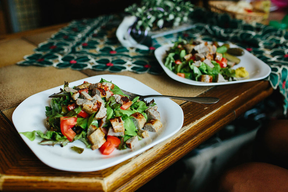 Bratwurst over salad.