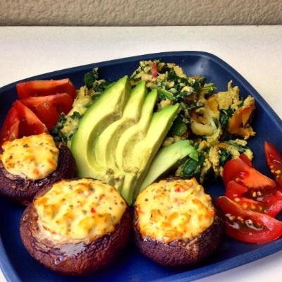Stuffed mushrooms with an egg and veggie scramble, fresh avocado, and sliced tomato.