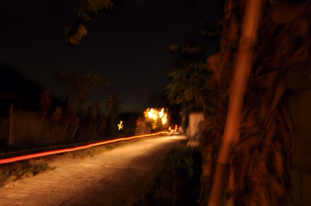 Long exposure shot of the festivities down the road - the long red streak on the left had side is a moped tail light that passed me on the lane.  Night photo!