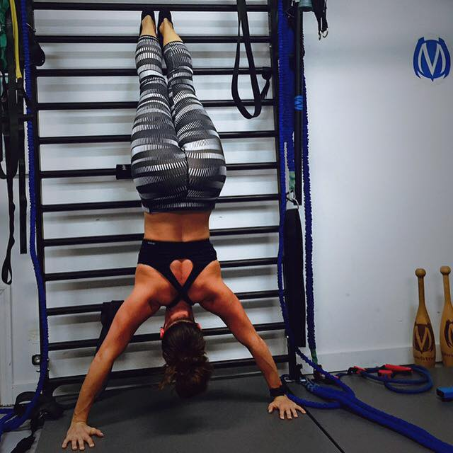 Using stall bars rungs to place feet at varied heights to support while maintaining and finding balance during handstand exercises
