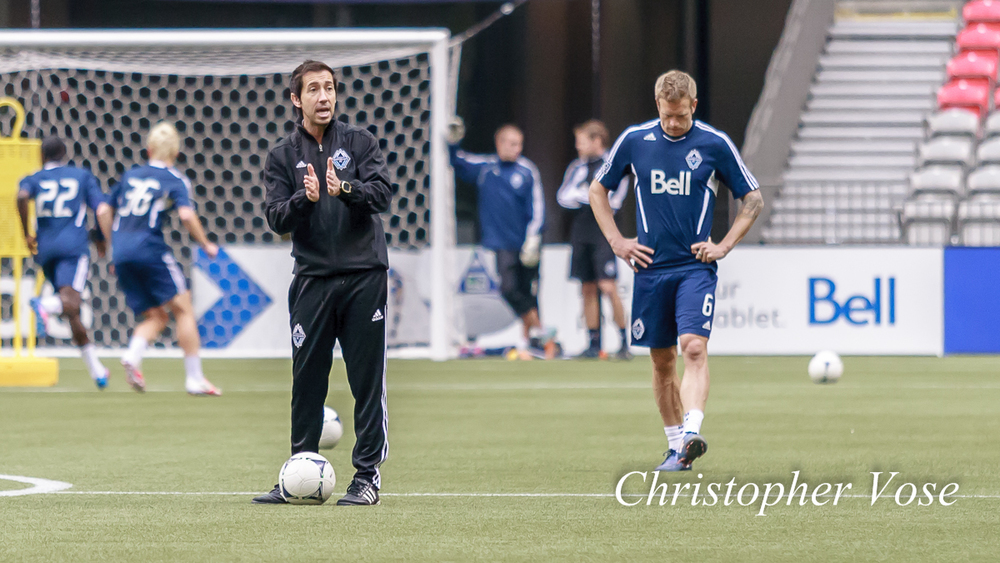 Martin Rennie coaches as Jay DeMerit takes a moment during Vancouver Whitecaps FC training at BC Place on 7 June 2012.