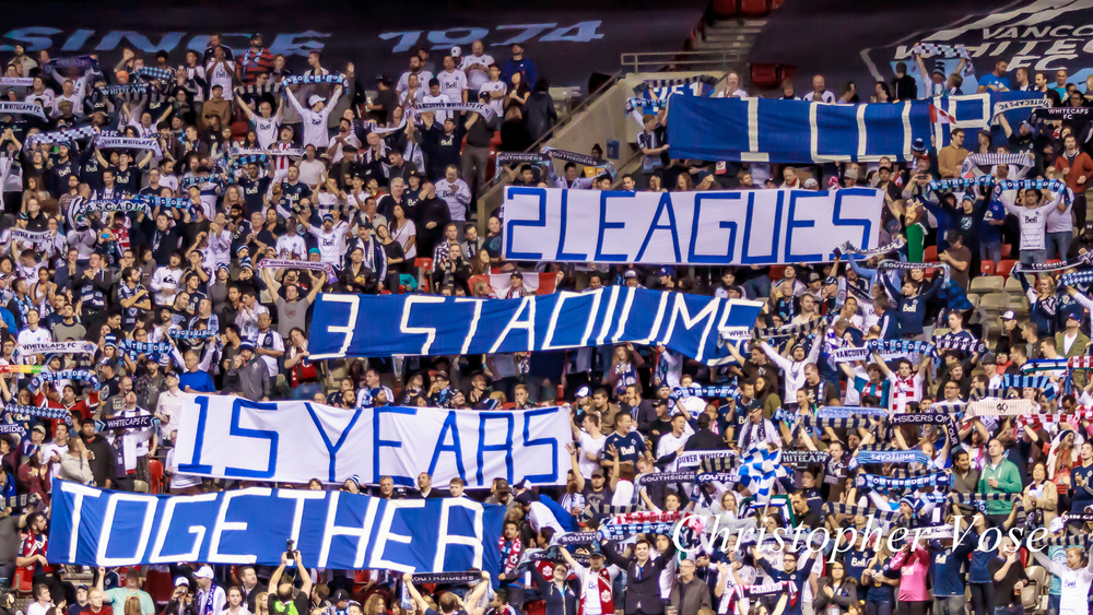 "The Vancouver Southsiders celebrated fifteen years of supporting football in Vancouver. Editor's note: The top line of the banner is partially obscured by supporters, but it should be read as ""1 club""."