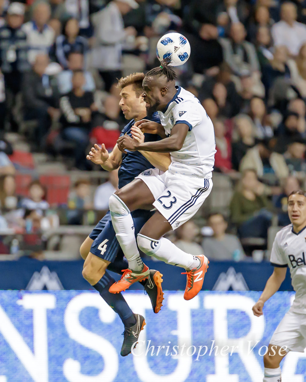 Kei Kamara contracts his body to give David Romney a sporting chance in their aerial duel at BC Place