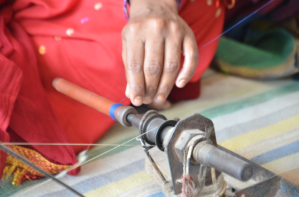 A woman from the family hand spins spools of thread for the bana (weft) part of hand loom weaving