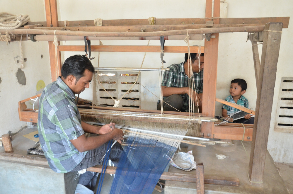 Damji Bhai (foreground) works on joining yarn to the hand loom while Purshotham Bhai (background) chats with his son