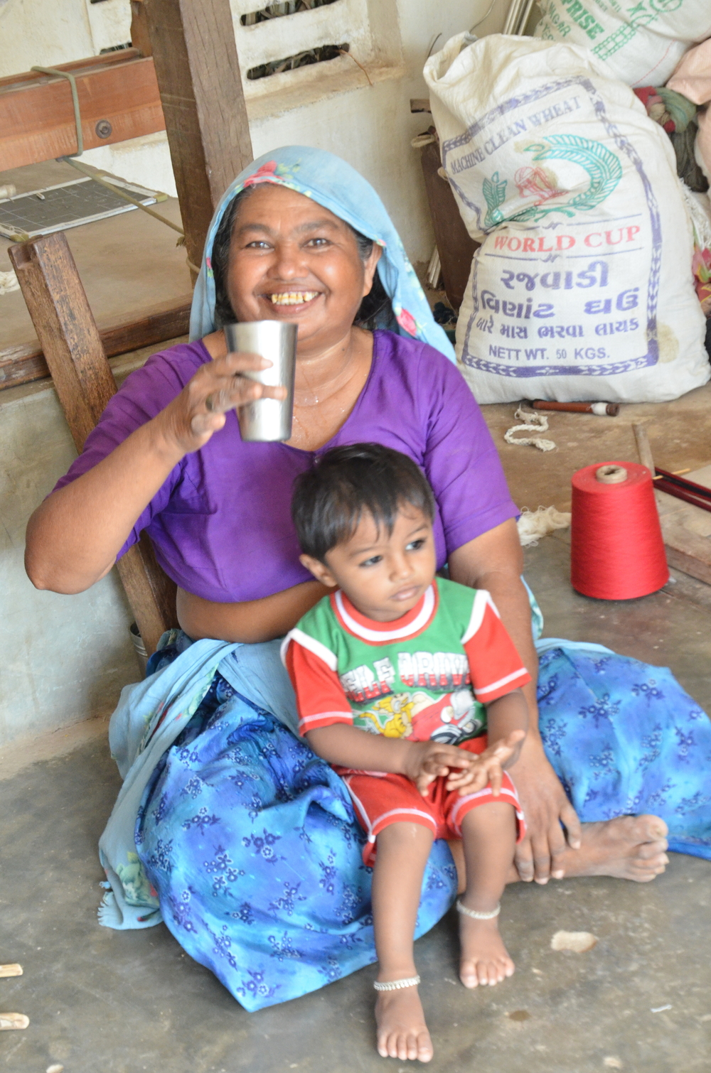 MaaJi, the mother and head of the KOR family household, pictured here with her grandson, Dux. Like her daughters-in-law, she plays a major role in enabling the family to uphold its weaving tradition.