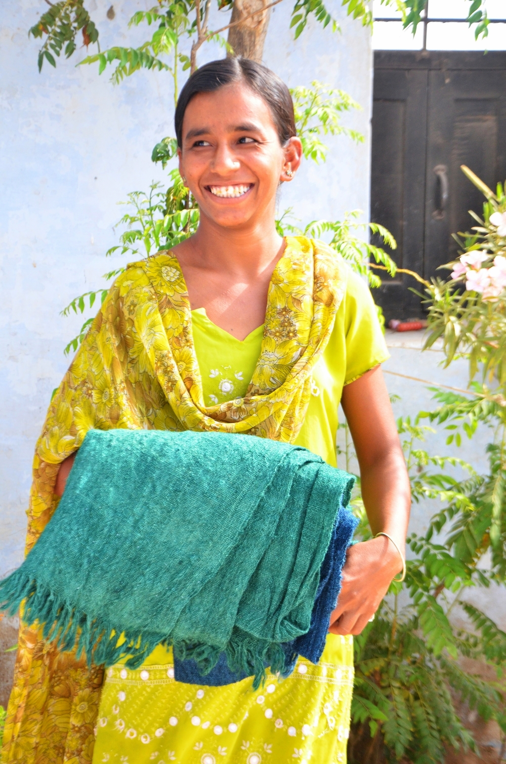 Local village women receive employment through their connection to ShyamJi Bhai's family. This lovely lady was responsible for doing the finishing work on our pure sheep wool scarves.