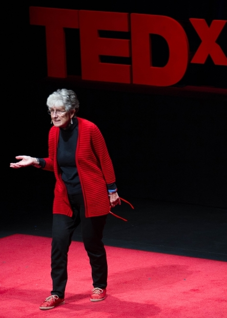 Monique Sternin presenting at TEDxMidAtlantic, October 2013, with red glasses in hand.