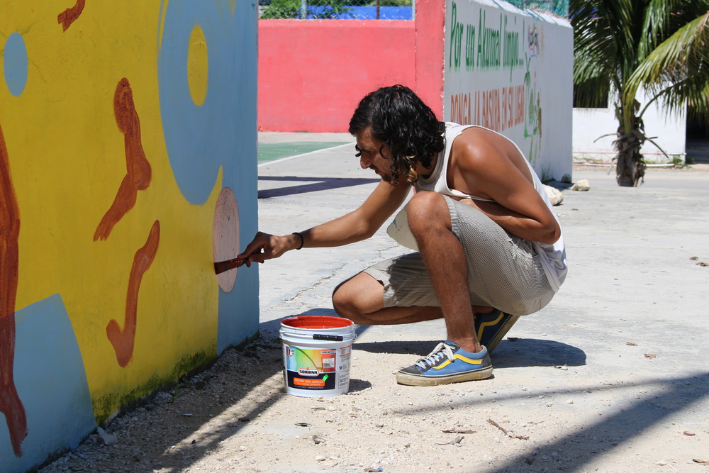 Michael working on his mural in the pueblo.