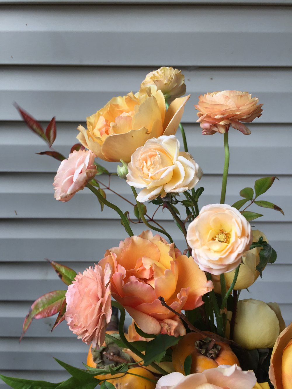 roses and ranunculus in peach and orange | wild green yonder